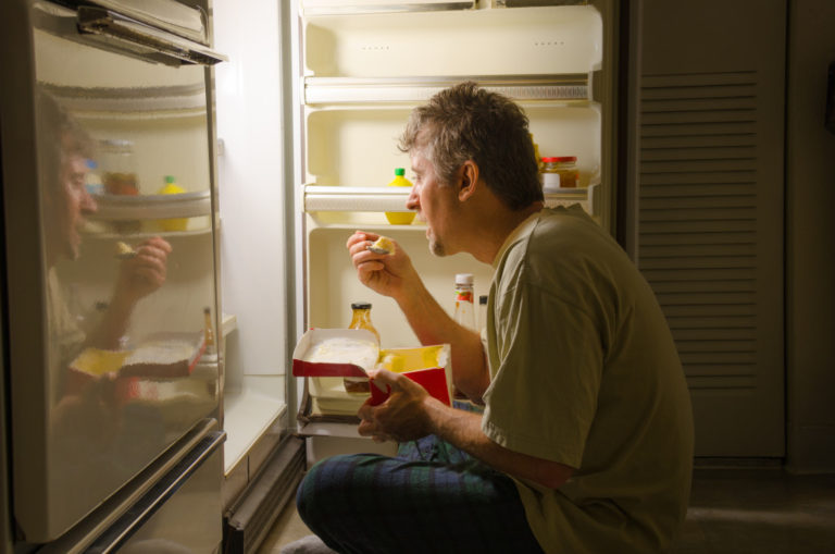 A man who has nighttime sleep-related eating disorder sleep eating as he sits in front of a refrigerator eating ice cream out of carton