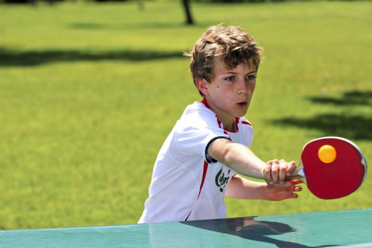 child playing table tennis outdoors