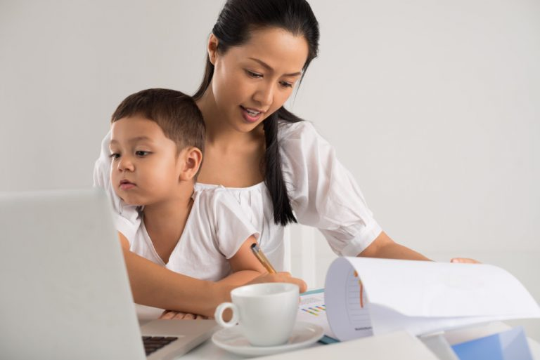 mom working while taking care of child